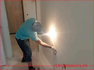 Мастер выравнивает стены в квартире
