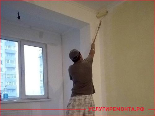 Процесс покраски стены в комнате