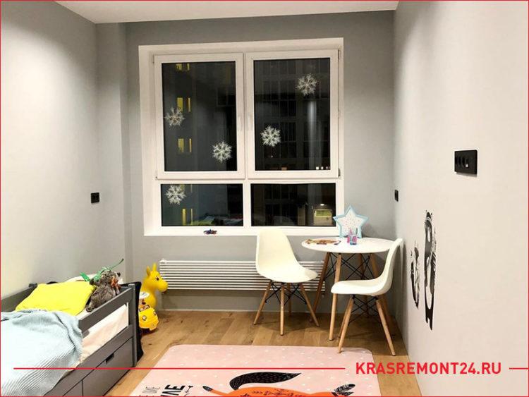 Дизайн детской комнаты с серыми стенами, столиком и кроватью