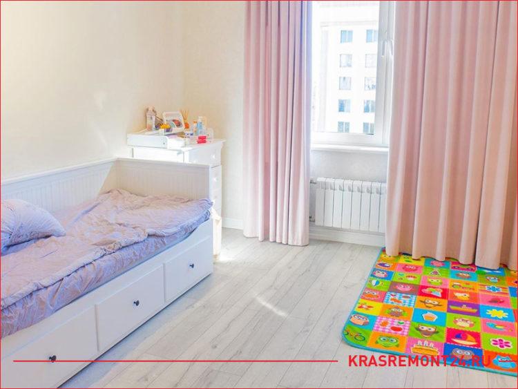 Детская кроватка и коврик для игрушек в комнате