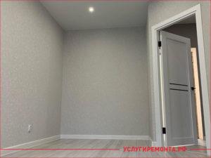Стены комнаты покрашены в серый цвет и коричневый ламинат