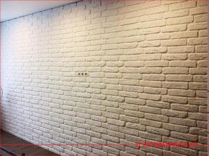 Стена в гостиной декорирована камнем