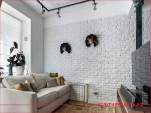 Стена в комнате украшена белым декоративным камнем