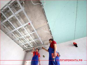 Два монтажника крепят листы гипсокартона на потолке